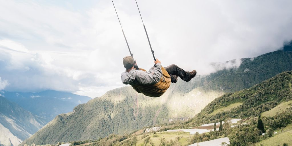 man swinging over a cliff at the  swing at the end  of the world in baños ecuador