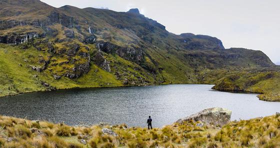Homem olhando para o lago no Parque Nacional Cajas, Equador